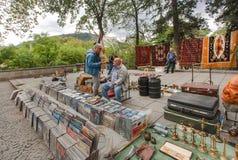 Venditore dei dischi di vinile che aspettano i compratori di musica al mercato delle pulci popolare a Tbilisi Immagine Stock