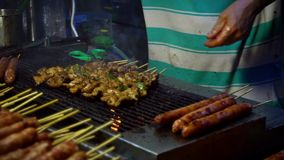 Venditore del movimento lento che cucina pollo di Taiwan sul bastone Via del mercato di notte archivi video