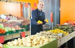 Venditore dell'uomo con il limone in negozio di verdure Fotografia Stock