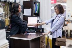 Venditore della donna nel deposito interno del tessuto con il cliente fotografia stock