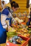 Venditore della ragazza circa il contatore con le case di pan di zenzero ricce Fotografia Stock Libera da Diritti