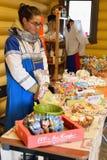 Venditore della ragazza circa il contatore con le case di pan di zenzero ricce Immagini Stock Libere da Diritti