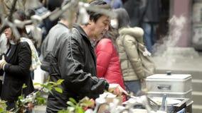 Venditore di alimento che cucina al festival religioso tradizionale stock footage