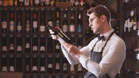 Venditore elegante del vino che tiene una bottiglia di vino e che legge etichetta in un deposito di vino stock footage