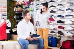 Venditore femminile che dimostra le scarpe da tennis al cliente nel deposito di sport fotografie stock libere da diritti