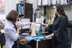 Venditore femminile che parla con il compratore in deposito dei tessuti e degli accessori per le tende, sala d'esposizione intern immagine stock libera da diritti