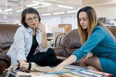 Venditore femminile che parla con il compratore in deposito dei tessuti e degli accessori per le tende, sala d'esposizione intern fotografia stock