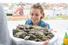 Venditore femminile sorridente dell'ostrica fotografie stock libere da diritti