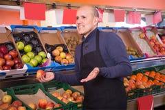 Venditore maschio impegnato che vende le mele nella drogheria Fotografia Stock