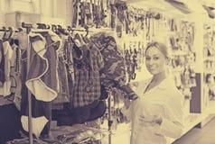 Venditore professionista della ragazza che consiglia sui vestiti per gli animali domestici Fotografie Stock Libere da Diritti