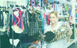Venditore professionista della ragazza felice che consiglia sui vestiti per gli animali domestici Fotografia Stock