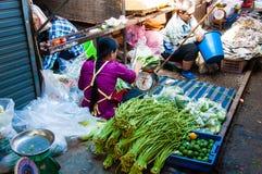 Venditori ambulanti sul mercato famoso della ferrovia di Maeklong Ogni volta che un treno si avvicina a, le tende e la s Immagini Stock Libere da Diritti