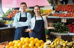 Venditori positivi che hanno le verdure e frutta sulle esposizioni Immagini Stock Libere da Diritti