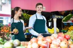 Venditori positivi che hanno le verdure e frutta sulle esposizioni Fotografia Stock