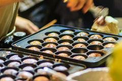 Vendor is cooking for Khanom khrok or coconut-rice pancakes, one Royalty Free Stock Photography