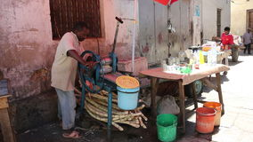 Vendor extracting juice from sugarcane stock video footage