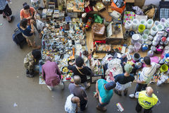 Vendor in flea market (Barcelona, els encants). Barcelona, Spain - June 18, 2014: Post of objects, antiques, and furniture resale while several clients are stock images