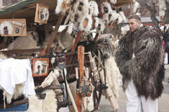 Vendor in fur coat with street bazar at a carnival. Carnival in MOHÁCS, HUNGARY - FEBRUARY 19: Vendor in fur coat with street bazar at the carnival of funeral Royalty Free Stock Images