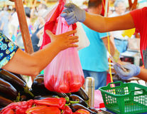 Vendor hands over a plastic bag to the buyer. Vendor hands over a plastic bag to a buyer filled with tomatoes at the market royalty free stock photo