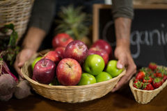 Vendor holding a basket of apples at the grocery store. Close-up of a vendor holding a basket of apples at the grocery store Royalty Free Stock Photo