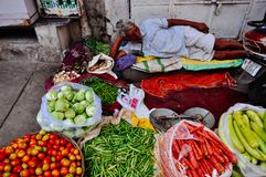 A vendor lays in the shade in Jaipur, India. A vendor lays in the shade in with his vegetables in Jaipur, India stock image