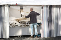 Vendor measures amount of fabric in market stall Stock Images