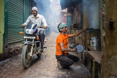 Vendor and motorcyclist. VARANASI, INDIA - 20 FEBRUARY 2015: Street vendor makes fire for milky tea in coal oven while motorcyclist passes by Stock Image