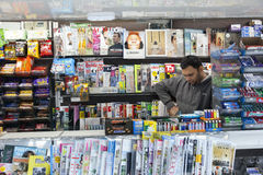 vendor of newspapers and magazines reads while waiting for customers stock images