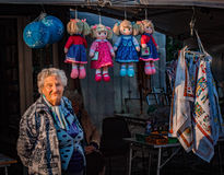 Vendor. An old woman selling dolls Royalty Free Stock Photography