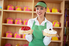 Vendor in pastry shop hold two nice cakes in hands. Female attractive vendor in pastry shop hold two nice cakes in hands Royalty Free Stock Images