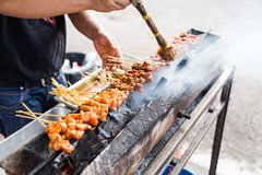 Vendor preparing chicken and beef barbecue satay on charcoal gri. Vendor preparing delicious barbecue chicken and beef satay on charcoal grille with shallow Royalty Free Stock Photo