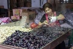 Vendor preparing water chestnuts. NEW TAIPEI CITY, TAIPEI, TAIWAN. NOVEMBER 2, 2014. Taiwanese vendor preparing water chestnuts at a street market in Taiwan stock photo