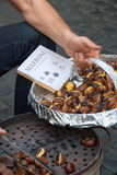 Vendor in Rome offering roasted chestnuts to tourists. Vendor in Rome, Italy offering roasted chestnuts to tourists. The sign reads 'Brown cooked on the grill Royalty Free Stock Image