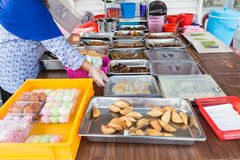 Vendor selling assorted Malay sweet cakes food at street stall Stock Photography