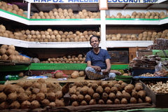 Vendor sits behind a large pile of coconuts  in New Market in Kolkata. Vendor sits behind a large pile of skinned brown coconuts  in New Market in Kolkata, India Royalty Free Stock Photo