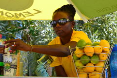 Vendor at St Maartin Bahamas. This is a vendor just outside  where the Cruise ship is docked.  One of many open air shops right on the dock.  She is mixing the Royalty Free Stock Images