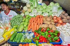Vendor at a stall selling a variety of vegetables royalty free stock photos