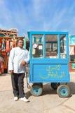 Vendor on the street next to standa Stock Image