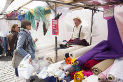 Vendor of textiles in dutch market stall Stock Photography