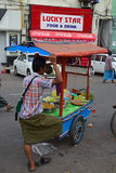 A vendor wearing traditional Burmese longyi selling fresh & pickled fruits in his movable stall Stock Photography