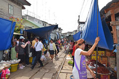 Vendors are keeping their stalls away from the coming train at Maeklong Railway Market. Stock Photos