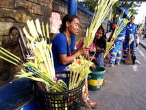 Vendors prepare palm leaves to be sold to church patrons in preparation for the Palm Sunday Stock Photography