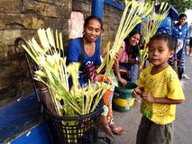 Vendors prepare palm leaves to be sold to church patrons in preparation for the Palm Sunday Stock Photo