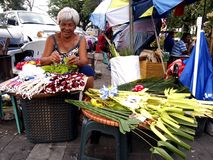 Vendors prepare palm leaves to be sold to church patrons in preparation for the Palm Sunday Royalty Free Stock Images