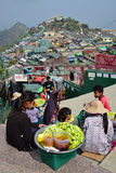 Vendors selling raw cut mango plus dark sauce and plum powder with large community over a small hill behind Royalty Free Stock Image
