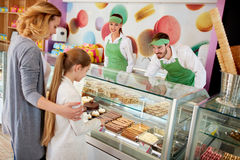 Vendors serves customers in candy store. Obliging vendors serves customers in candy store royalty free stock photos