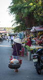 Vendors walking on street in Hoi An, Vietnam Royalty Free Stock Photos