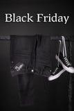 Vendredi noir Vente rose et jaune et les espadrilles blanches halètent, des jeans accrochant sur le fond de support de vêtements  Photo libre de droits