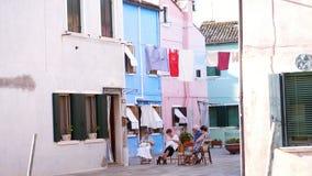 VENECIA, BURANO, ITALIA - 7 DE JULIO DE 2018: calle atmosférica en la isla de Burano Las personas mayores se sientan en la calle, almacen de video