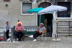 VENECIA 25 de agosto. Gondoleros el las vacaciones, sentándose debajo del paraguas Imagenes de archivo